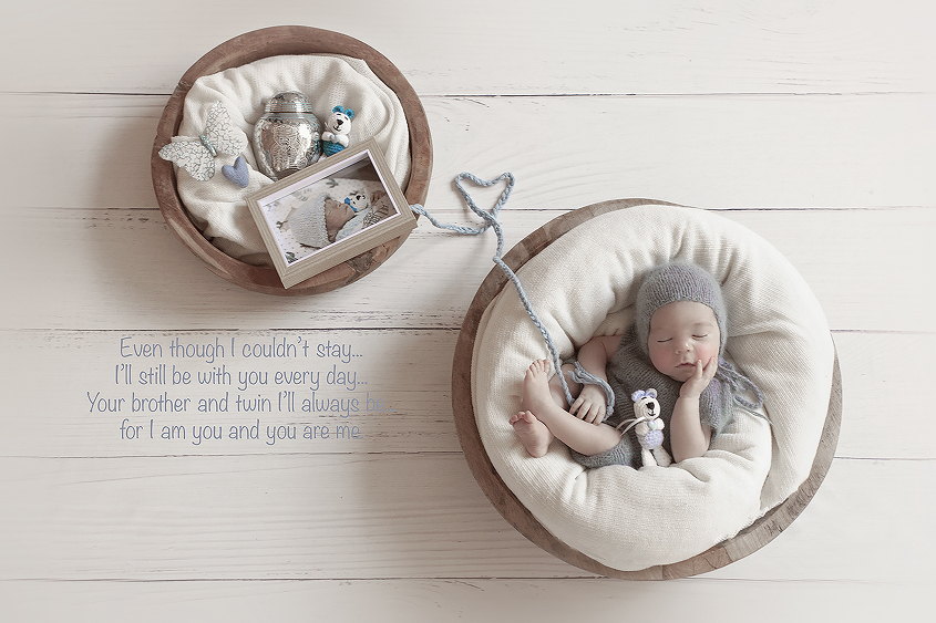 Newborn baby boy seeping in wooden bowl wearing blue knot romper and bonnet with cream blanket holding small knit bear and wool heart connecting baby to smaller wooden bowl containing cream wrap and small knit bear and felt heart and butterfly and urn and frame of deceased baby sibling