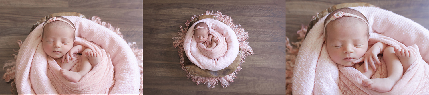 Newborn baby girl wrapped in pink wrap with pink curly felt in wooden log bowl on wooden floor