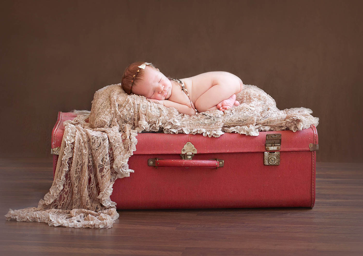 Newborn girl sleeping on red suitcase with brown lace wrap and bow tieback