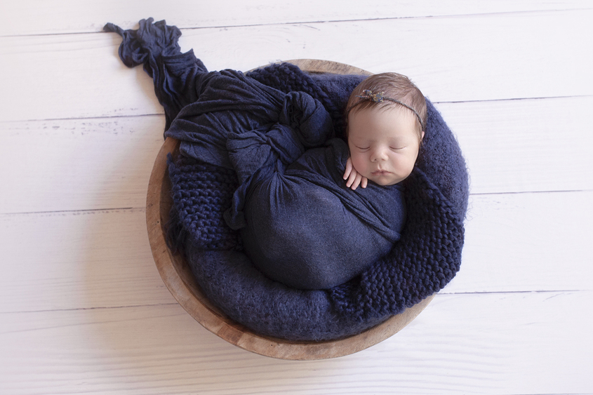 Newborn baby girl sleeping in round wooden bowl with navy wrap and knit layer and blanket and tieback on white wooden floor