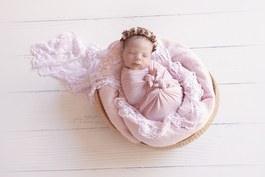 Newborn baby girl sleeping in oval wooden bowl on white wooden floor with pink blanket and wrap and lace wrap and flower tieback