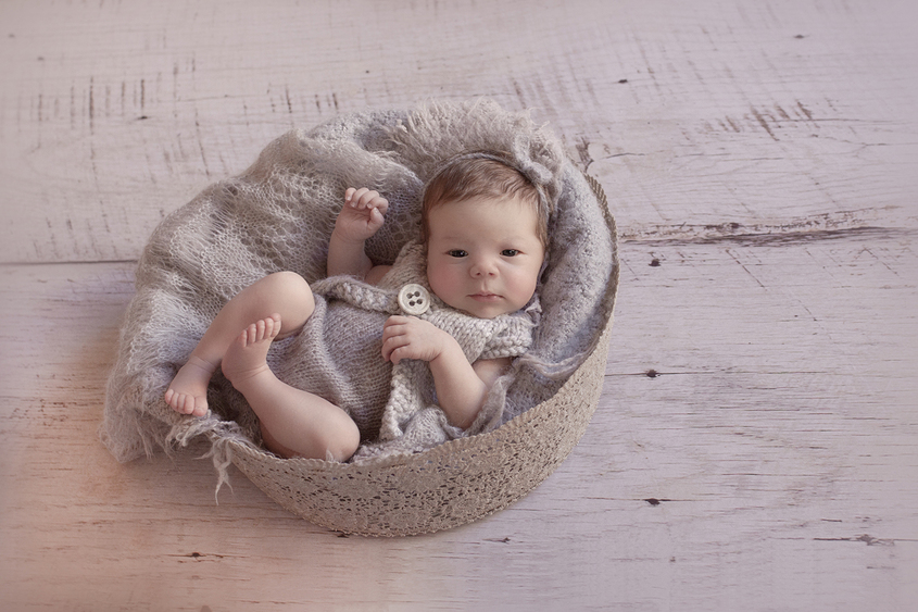 Newborn baby in grey lace bowl wearing grey knit clothes and flower tieback on wooden floor