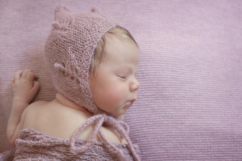 Newborn baby girl sleeping on purple blanket with purple tieback and wrap and bonnet