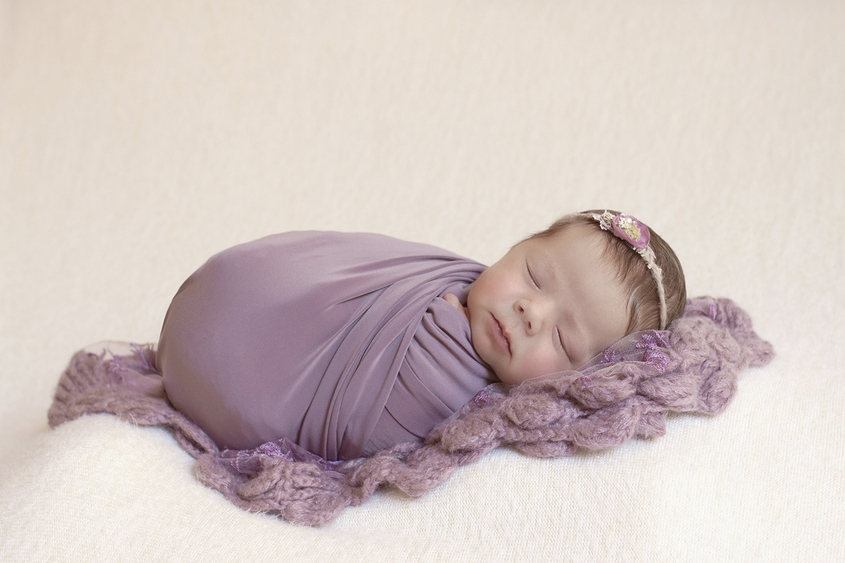 Newborn baby girl sleeping on cream blanket wrapped in purple wrap with purple lace blanket and flower tieback