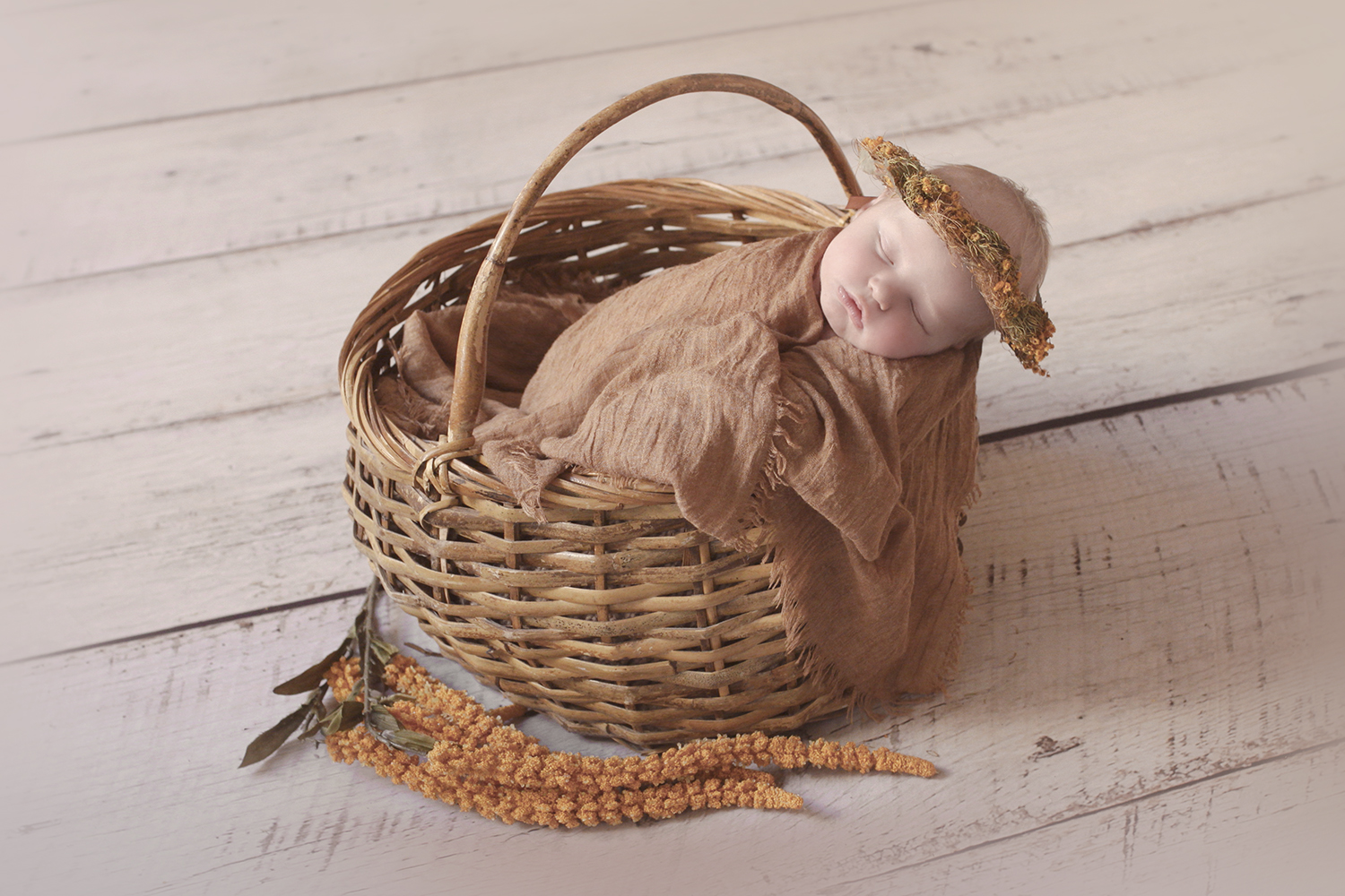Newborn baby girl sleeping in cane basket with mustard wrap and halo and flowers