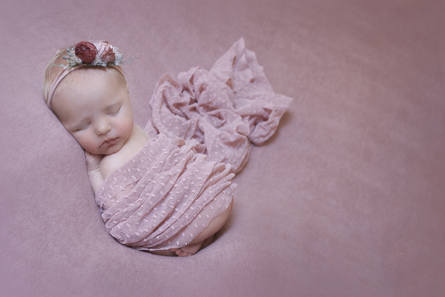 Newborn baby girl sleeping on pink blanket with pink lace wrap and pink flower tieback