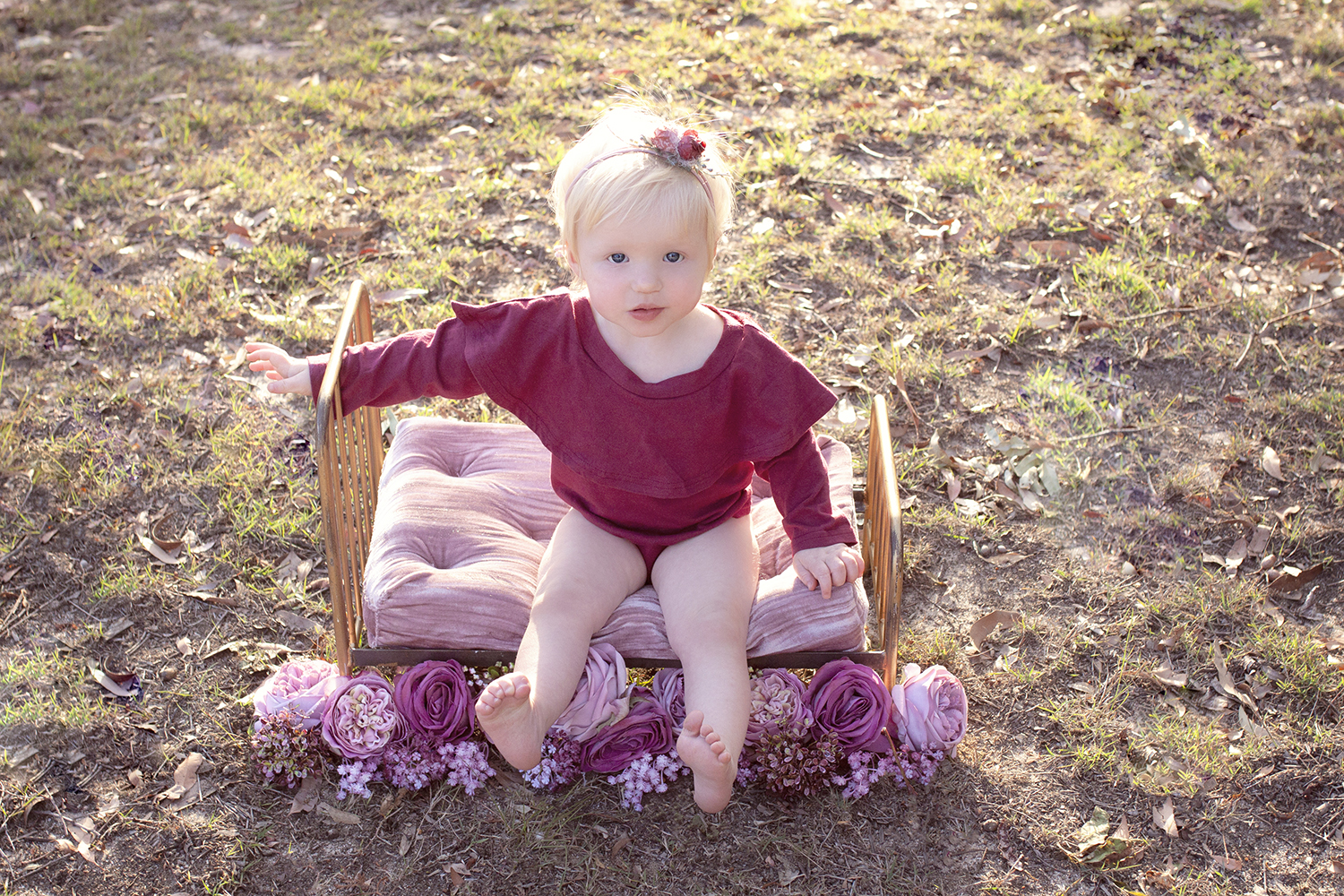 One year old baby girl sitting on vinatge gold iron bed in park at sunset wearing maroon romper with flower tieback sitting on pink velvet pillow surrounded by flowers