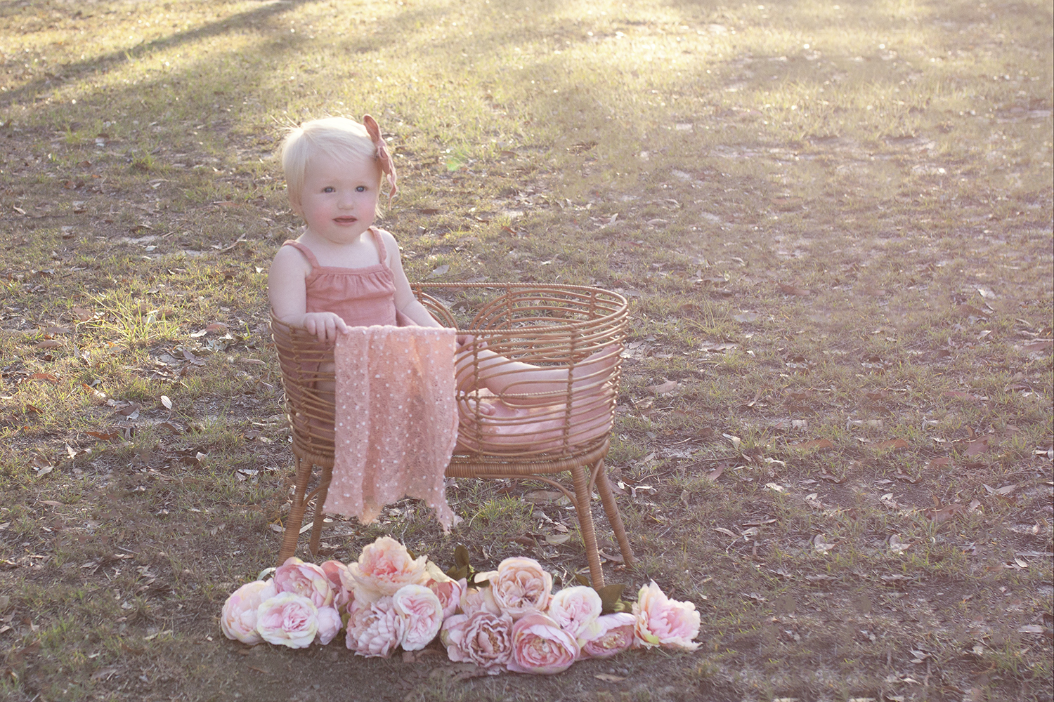 One year old girl in cane basket wearing peach romper and bow with peach blanket and flowers on grass at sunset
