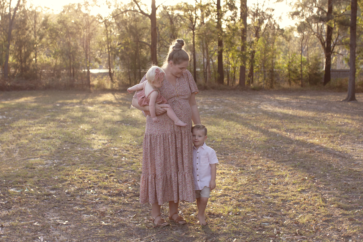 Pregnant mother wearing peach floral dress holding one year old girl wearing peach romper and bow and toddler sibling boy wearing white shirt and tan shorts in park at sunset