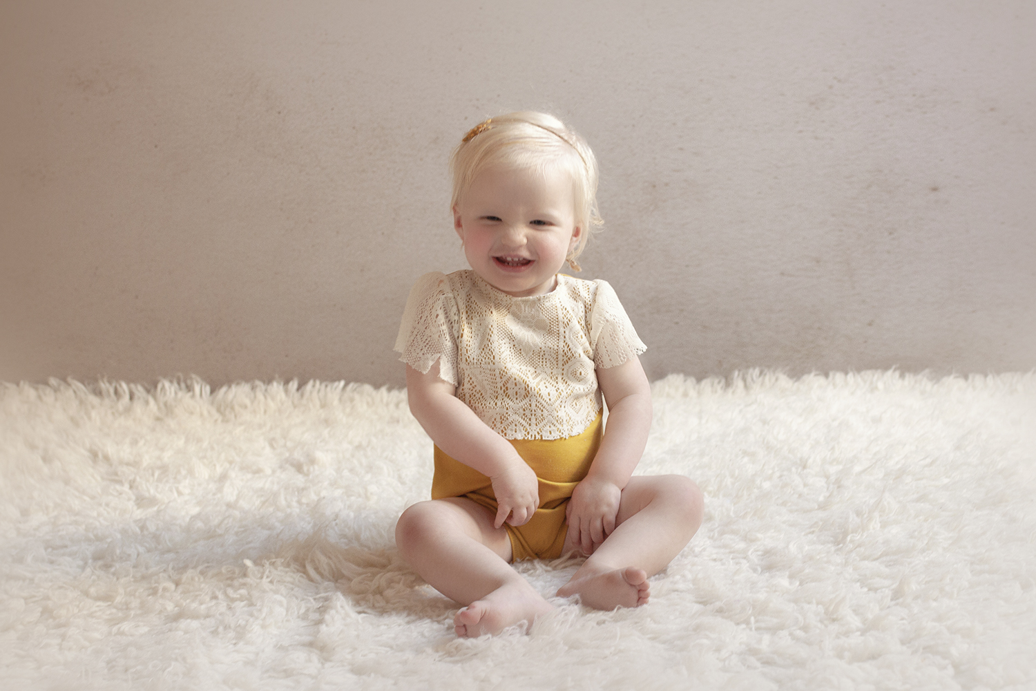 One year old girl wearing lace and mustard romper on cream flokati