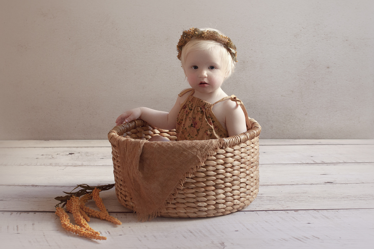 One year old girl in cane basket with brown romper and mustard flower halo and flowers on white wooden floor