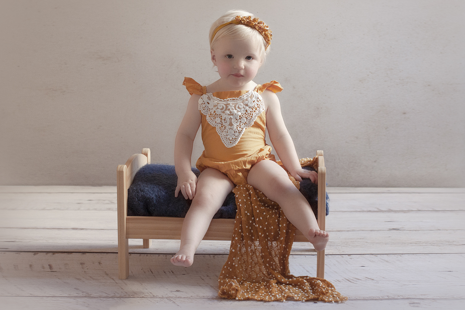 One year old girl wearing mustard romper and halo on wooden bed with navy blanket on white wooden floor