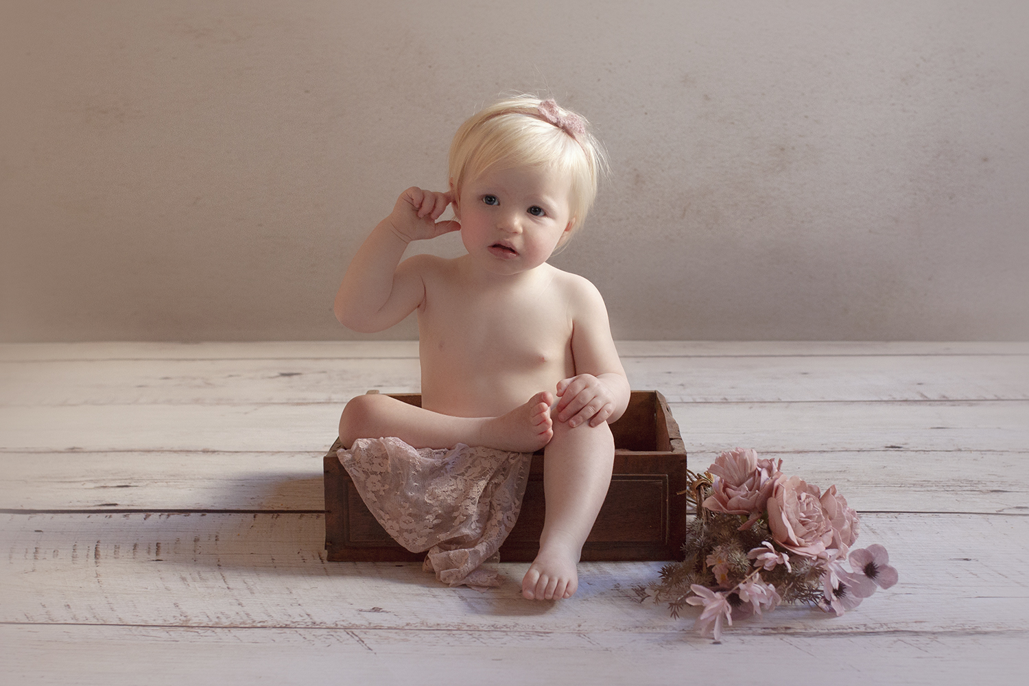 One year old girl with pink lace wrap and bow tieback in wooden drawer with pink flowers on white wooden floor