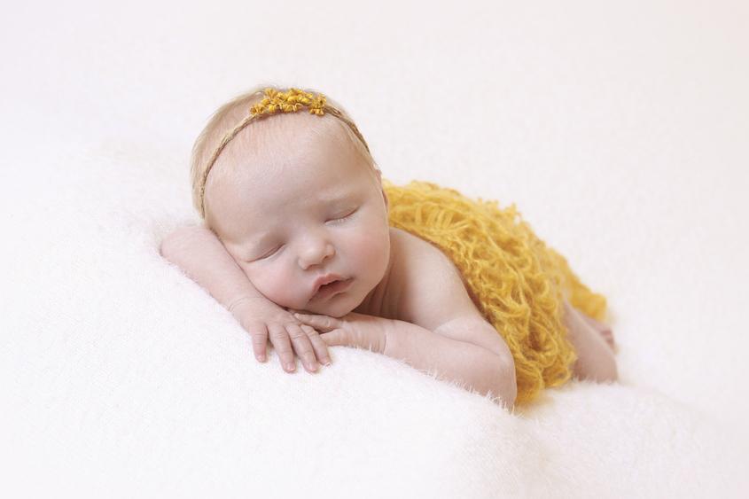 Newborn baby girl sleeping on cream blanket with mustard knit wrap and mustard flower tieback