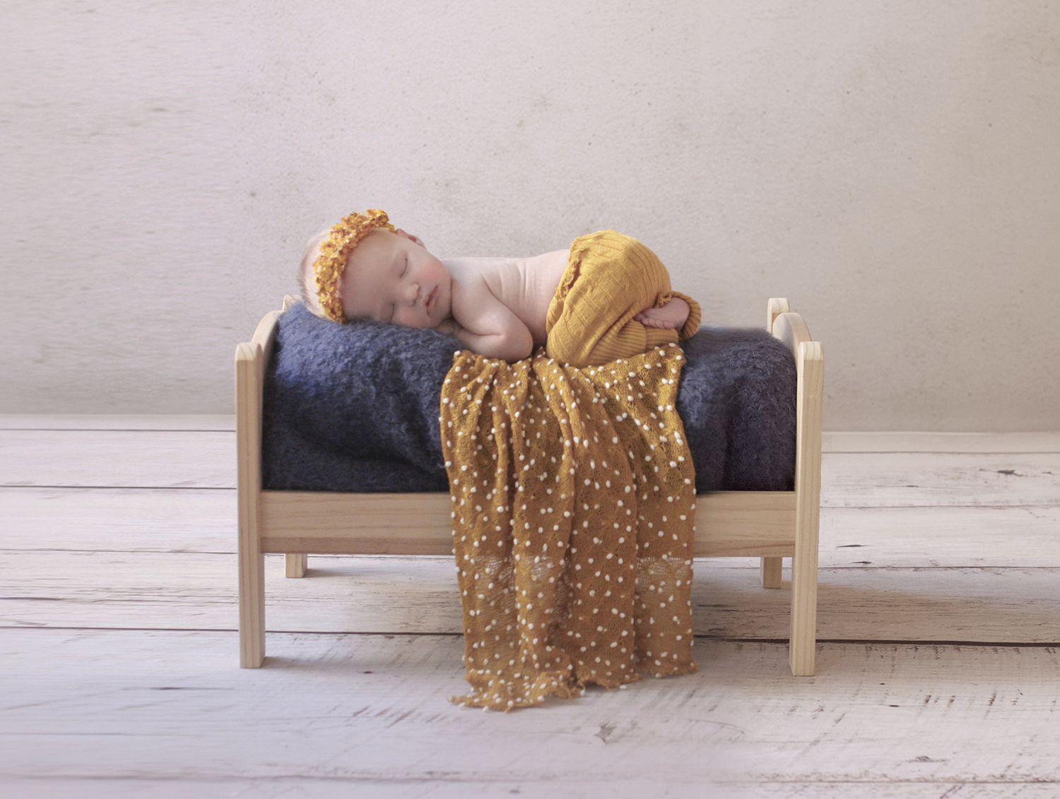 Newborn baby girl wearing mustard pants and halo on wooden bed with navy blanket and mustard wrap on white wooden floor