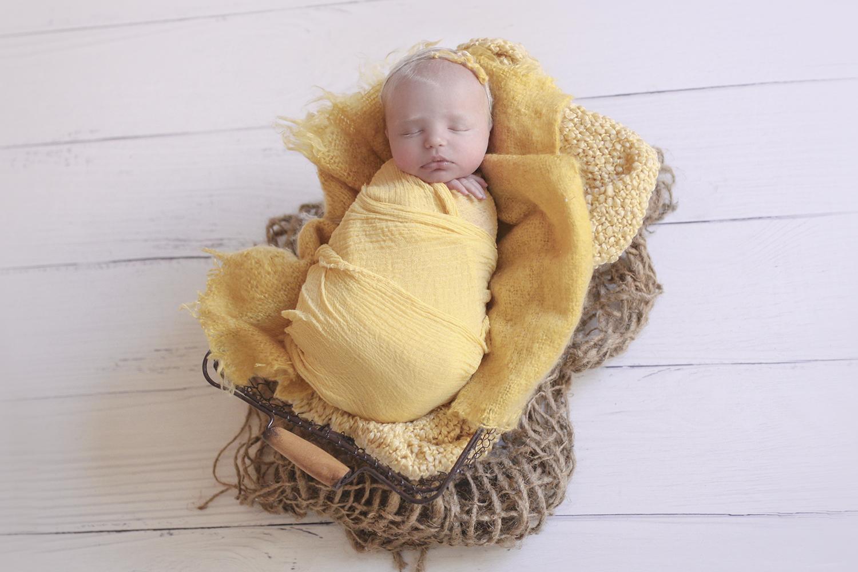 Newborn baby wrapped in mustard wrap with mustard blanket in farmers basket wearing mustard tieback on wooden floor