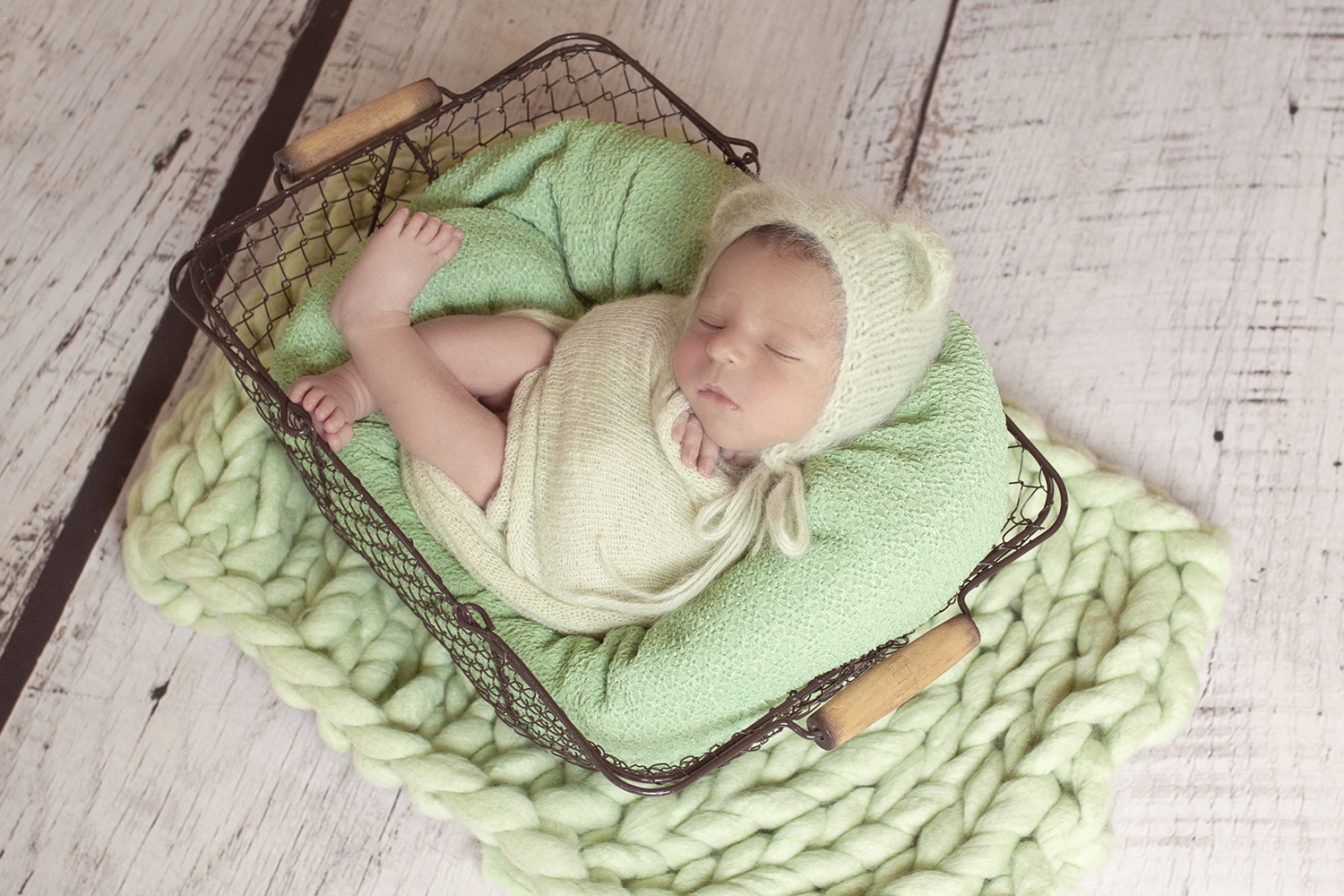 Newborn baby boy wrapped in green knit wrap sleeping in farmers basket with green blanket and green knit layer and bonnet on white wooden floor