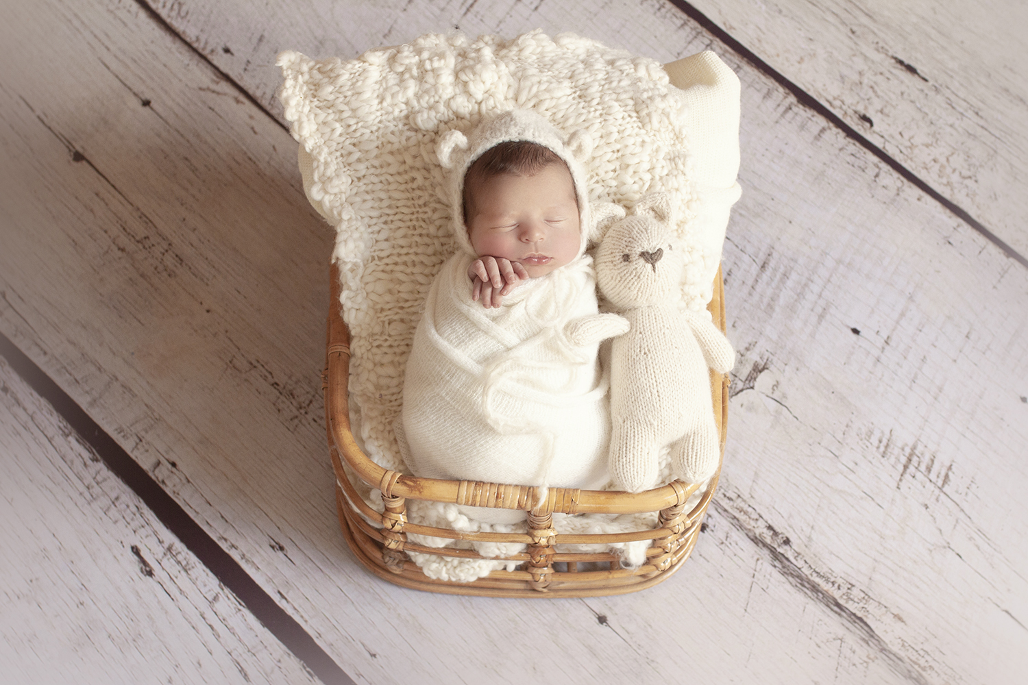 Newborn baby boy sleeping in cane basket with cream knit layer and wrap and bear beanie with bear on white wooden floor