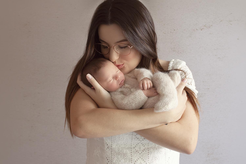 Mother holding newborn baby boy sleeping in cream knit romper