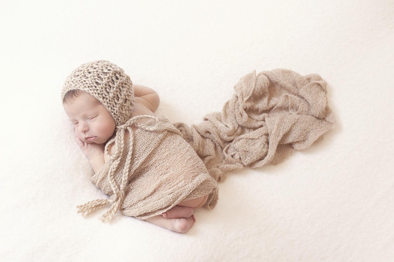 Newborn baby boy sleeping on cream blanket with tan wrap and knit bonnet