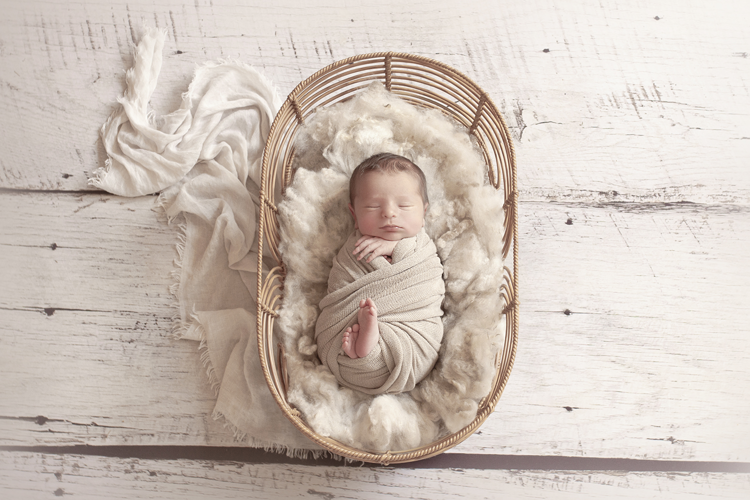 Newborn baby boy sleeping in oval cane basket with cream fur and blanket and wrap and knit bonnet on white wooden floor