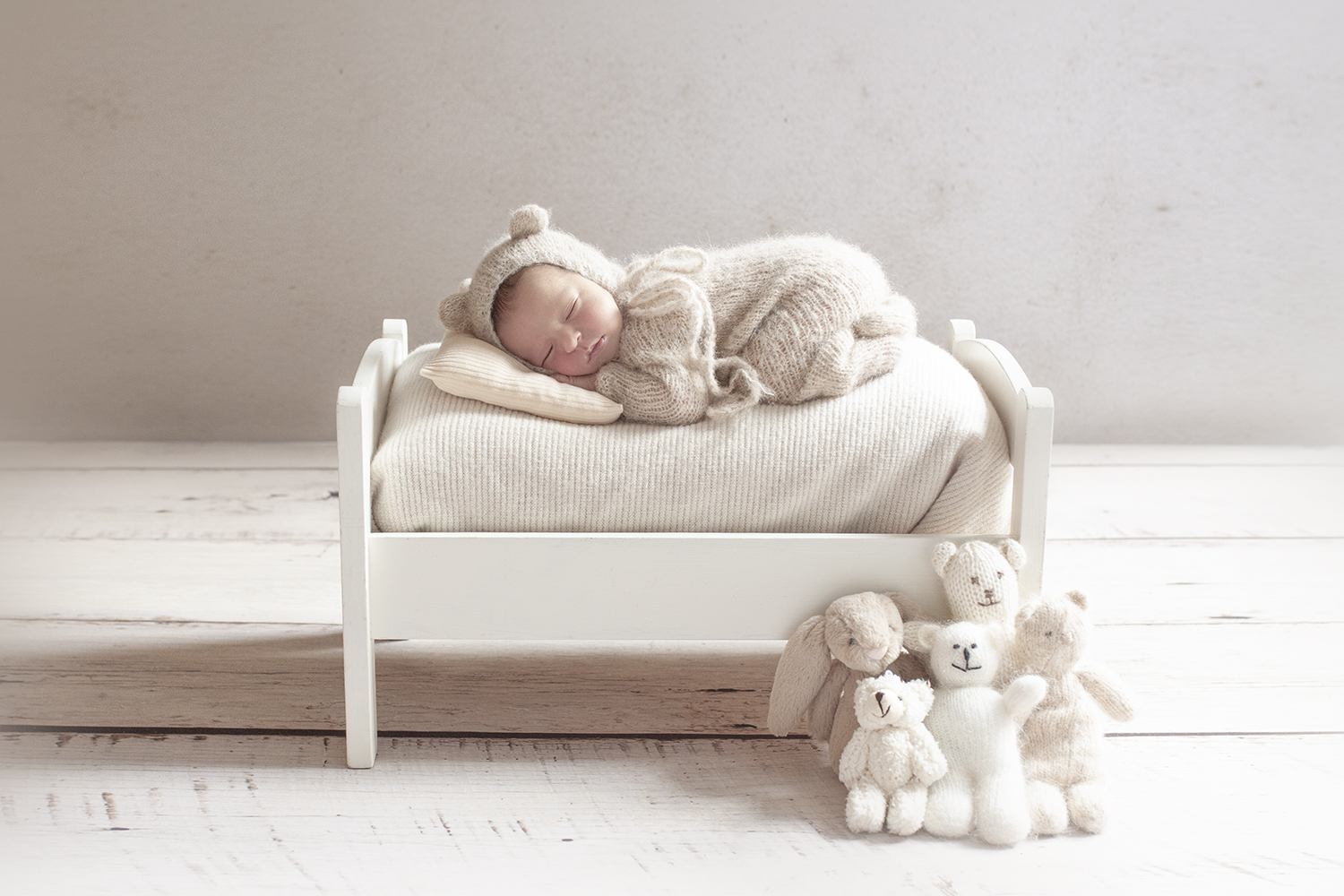 Newborn baby boy sleeping on white wooden bed wearing cream knit romper and bear beanie with bunch of teddy bears on white wooden floor
