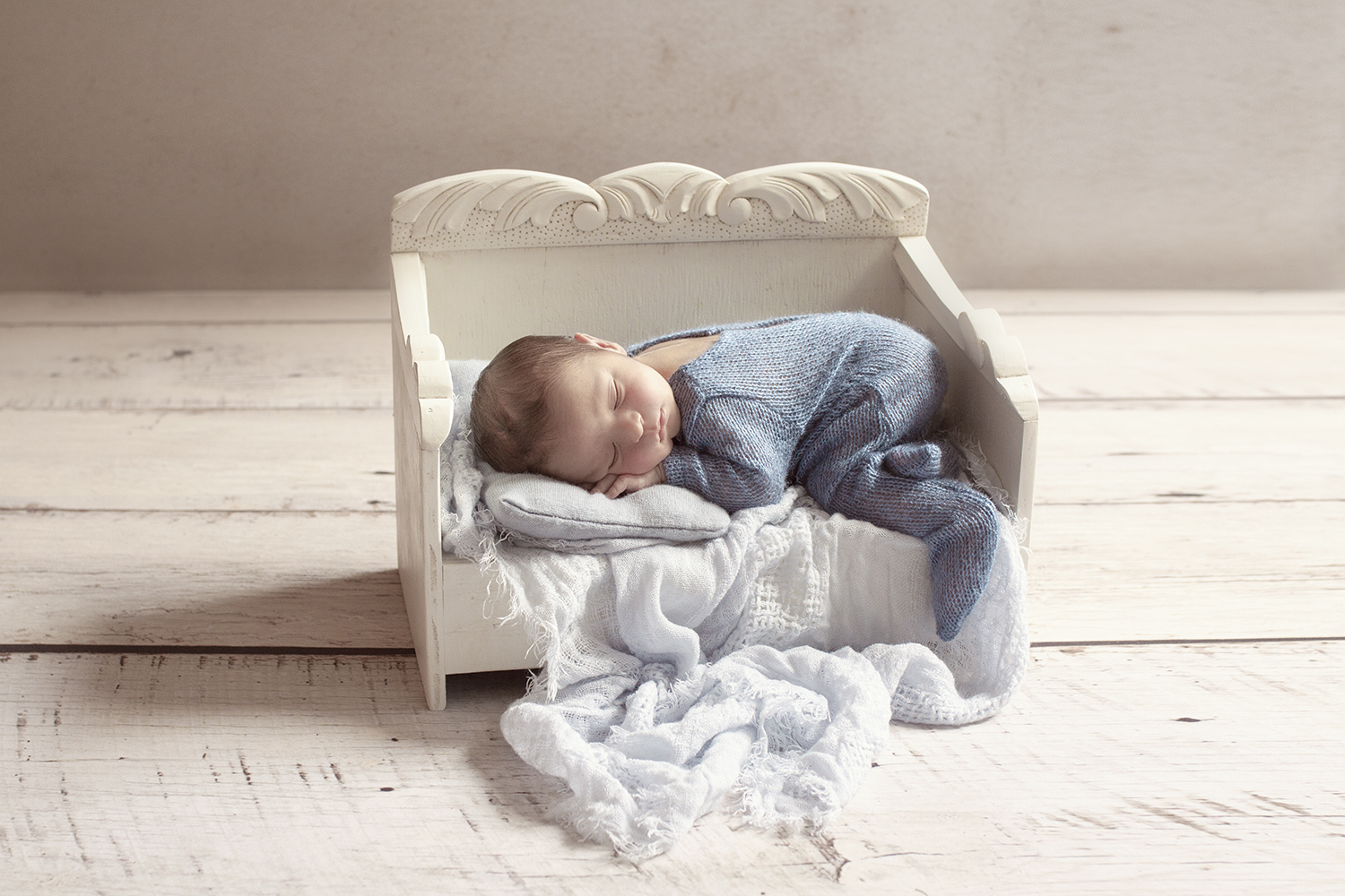 Newborn baby boy sleeping in cream wooden day bed wearing blue romper with blue wrap and pillow on white wooden floor