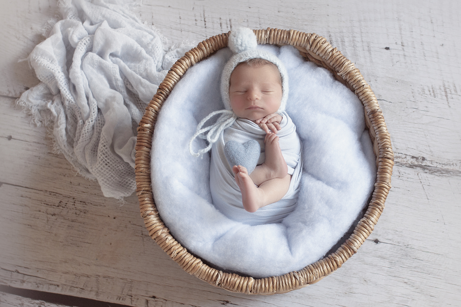 Newborn baby boy sleeping in round cane basket with blue fluff and wrap and felt heart and bonnet on white wooden floor