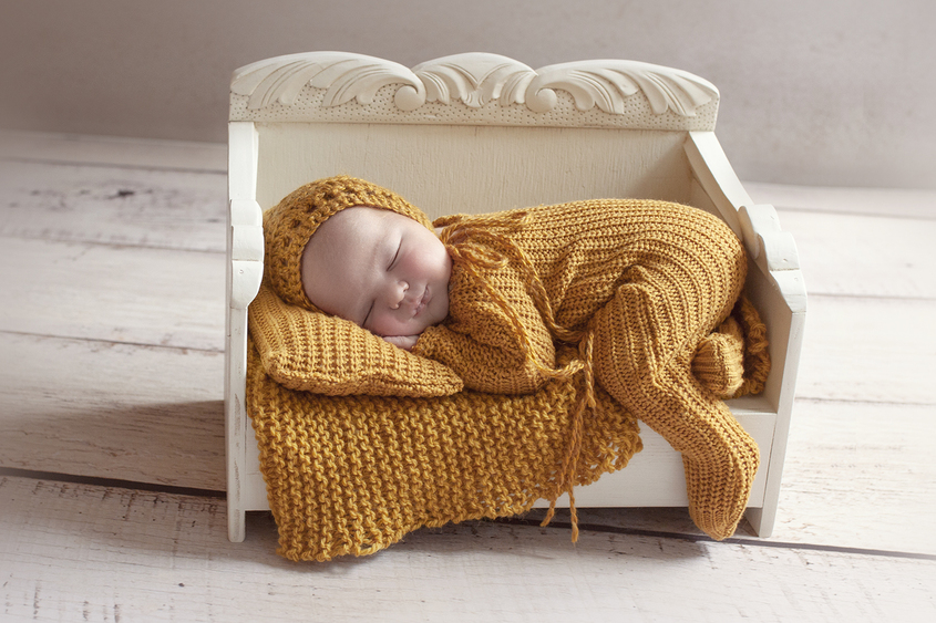 Newborn baby boy sleeping in white wooden day bed wearing mustard knit romper and beanie with knit pillow and wrap