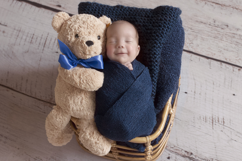 Smiling newborn baby boy sleeping in cane basket with navy wrap and blanket and knit layer with bear and blue ribbon on white wooden floor