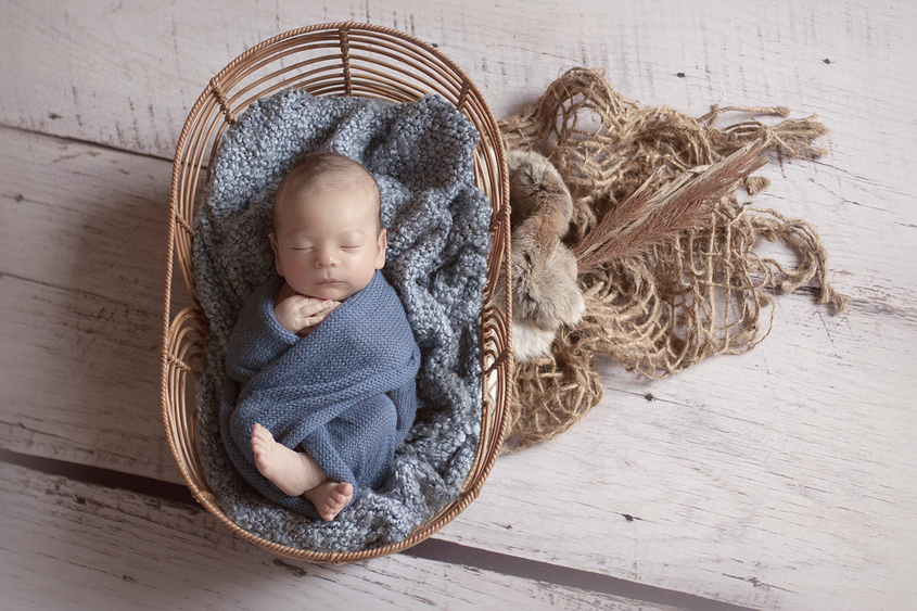 Newborn baby boy sleeping in oval cane basket with blue blanket and wrap and hessian layer with rabbit pelt and dried grass on wooden floor