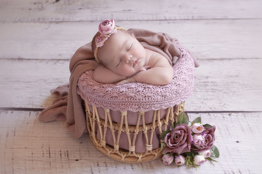 Newborn baby girl in round cane basket with pink knit wrap and pink blanket with flowers and wearing pink fower tieback