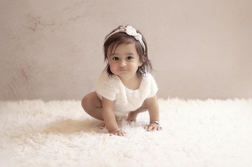 Nine month old baby wearing white knit romper and bow on cream fur