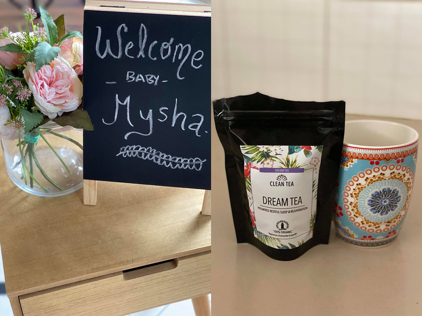Small blackboard with writing on in stating welcome baby Mysha with glass vase and pink flowers on small wooden table plus multi coloured coffee cup sitting beside bag of leaf tea