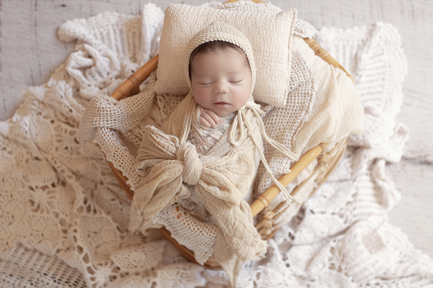 Newborn baby sleeping in cane basket with cream wraps and layers and tieback and bonnet