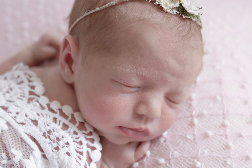 Newborn baby girl sleeping on pink spotted blanket with white lace wrap and flower tieback