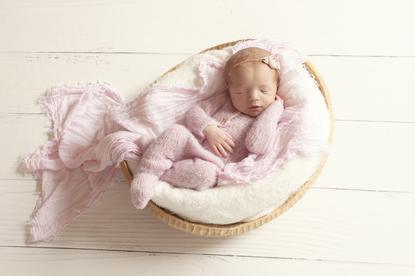 Newborn baby girl sleeping in oval wooden bowl with white blanket and pink wrap wearing pink knit romper and flower tieback on white wooden floor