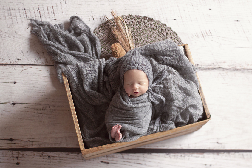Newborn baby boy sleeping in wooden crate with grey blanket and wrap and bonnet and lace layer and dried flowers on wooden floor