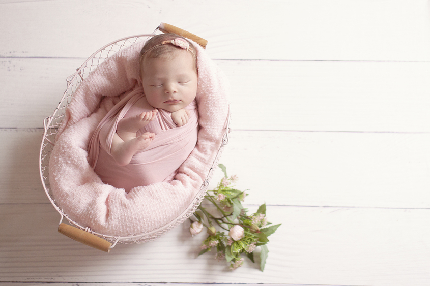 Newborn baby girl sleeping in pink farmers basket with pink blanket and wrap with flowers and tieback on white wooden floor