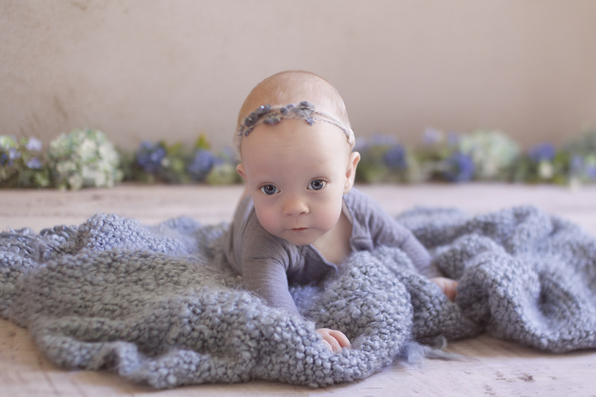 Nine month baby girl laying on blue blanket wearing blue romper and flower headband looking at camera with big blue eyes and blue green and white flowers in the background