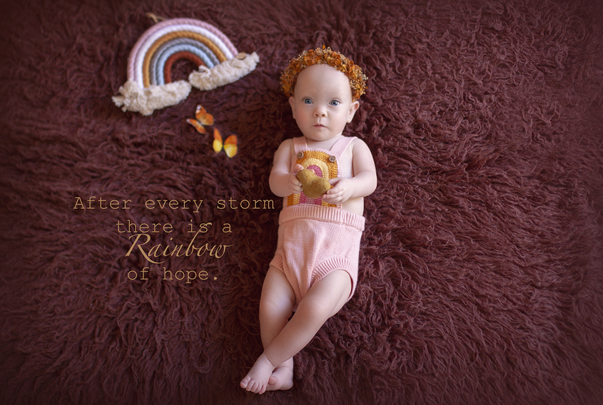Nine month baby girl laying on maroon curly fur wearing pink knit romper with rainbow on the front and mustard flower crown laying beisde two small orange butterflies and a rainbow hanging toy with saying typed on image After every storm there is a rainbow of hope