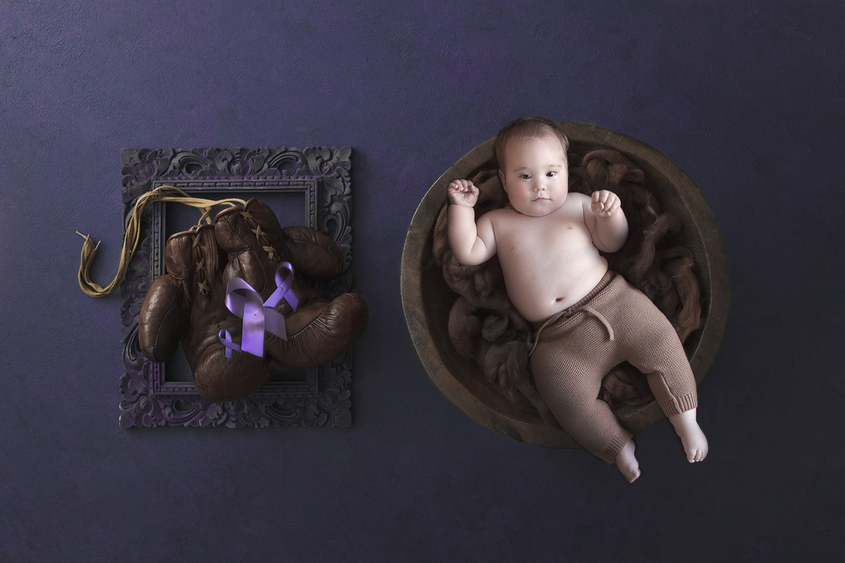 Eight month old baby boy laying in wooden bowl with brown felt and wearing brown pants on purple background with brown wooden frame with two brown leather gloves inside and 3 purple ribbons