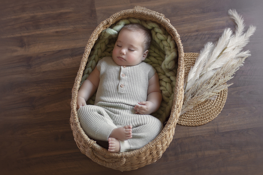 Eight month old baby boy sleeping in oval cane basket with sage green knit layer and wearing sage green knit romper with dried flowers on wooden floor