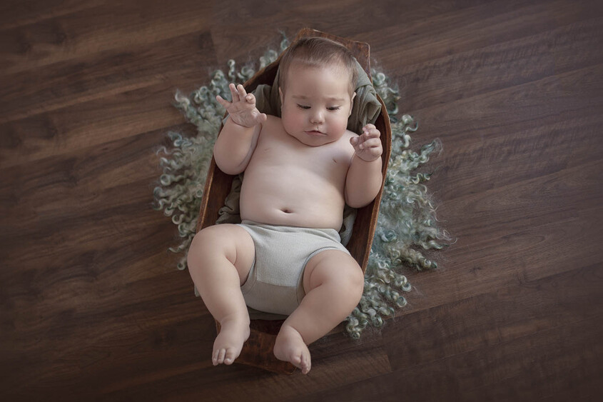 Eight month old baby boy in wooden trench bowl wearing sage green nappy cover on green curly felt on wooden floor