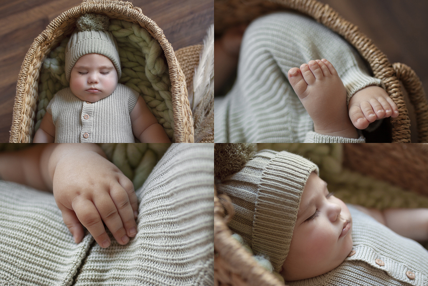 Eight month old baby boy sleeping in oval cane basket with sage green knit layer and wearing sage green knit romper and bonnet with dried flowers on wooden floor