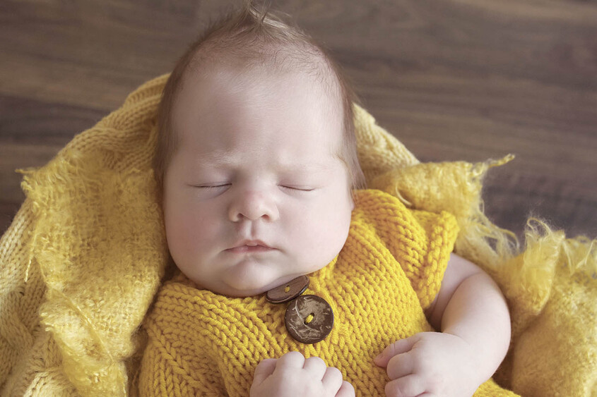 Newborn baby boy sleeping in farmers basket with mustard blanket and wearing mustard knit outfit on wooden floor