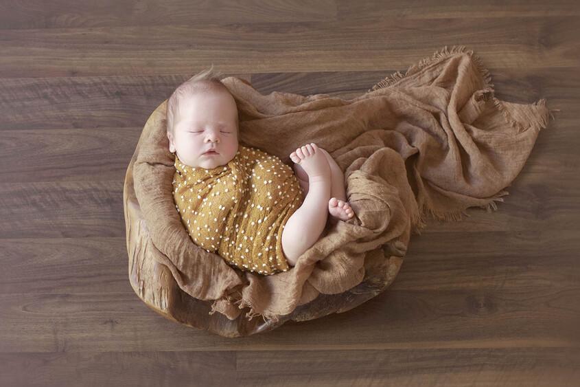Newborn baby boy sleeping in log bowl with mustard blanket and wrap on wooden floor