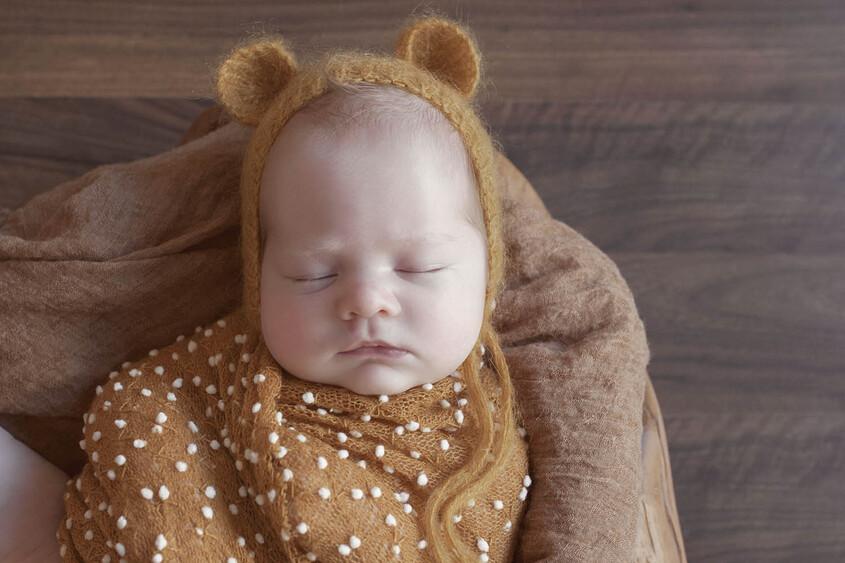 Newborn baby boy sleeping in log bowl with mustard blanket and wrap on wooden floor wearing mustard knit bear bonnet