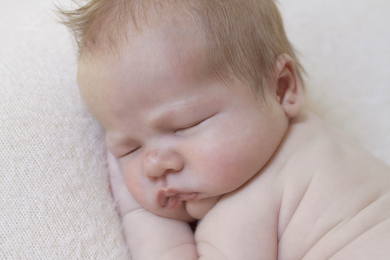 Newborn baby boy sleeping on cream blanket