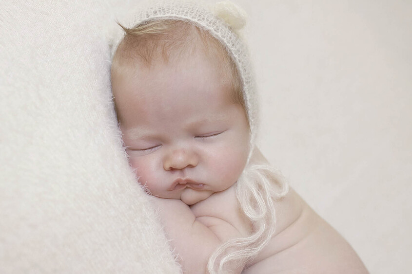 Newborn baby boy sleeping on cream blanket wearing cream knit bear bonnet
